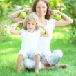 Happy family sitting on green grass and playing with fruits and vegetables in spring park. healthy eating concept — Stock Video #21381659