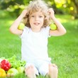 Stock Video: Happy child sitting on green grass and playing with fruits and vegetables in spring park. healthy eating concept
