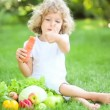 Royalty-Free Stock Obraz wektorowy: Happy child eating vegetables in spring park. Healthy eating concept