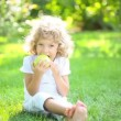 Stock Video: Happy child eating green apple in spring park. Healthy lifestyle concept