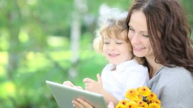Happy family using tablet PC outdoors in spring park — Stock Video