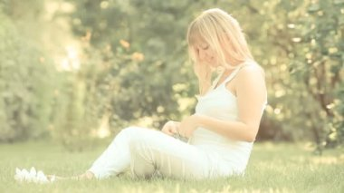 Pregnant woman playing with bootee in spring park. Slow motion, retro toned — Stock Video