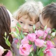 Happy family with bouquet of spring flowers — Stock Photo