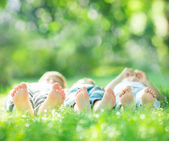 Family lying on green grass — Stok fotoğraf