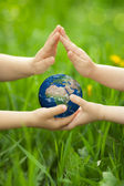 Planet Earth in childrens hands — Stock Photo
