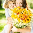 Happy family with spring flowers — Stock Photo