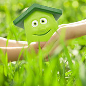Eco cartoon house in hands — Stock Photo