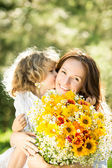 Woman and child with bouquet of flowers — Stock Photo