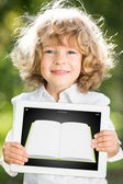 Child holding tablet PC with ebook — Stock Photo