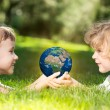 Earth in childrens hands — Stock Photo