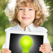 Child holding tablet PC with lightbulb - Stock Photo