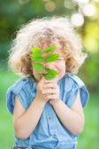 Child holding young plant — Stock Photo