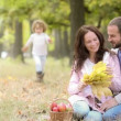 Happy family enjoying time together in the park during a beautiful autumn day — Stock Video