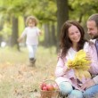 Happy family enjoying time together in the park during a beautiful autumn day — Vídeo de stock