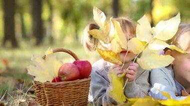 Three kids and a basket of red apples in an autumn park — Stock Video