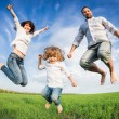Happy active family jumping — ストック写真