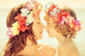 Vrouw en kind dragen hawaiiaanse bloemen garland — Stockfoto
