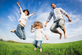 Happy active family jumping — Stockfoto