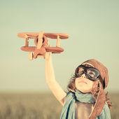 Bambino felice giocare con aeroplanino giocattolo — Foto Stock