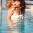 Stock Photo: Child kissing woman in pool