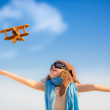 Happy kid playing with toy airplane — Stock Photo #27033555