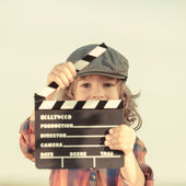 Kid holding clapper board in hands — Stok fotoğraf