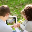 Stock Video: Happy family using tablet PC outdoors in autumn park