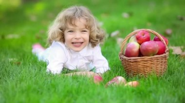 Happy child with red apples in autumn park — Stock Video