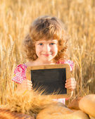 Happy child with bread in field — Stock Photo