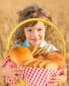 Child holding bread in basket — Stock Photo