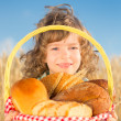 Happy child with bread in basket — Stock Photo