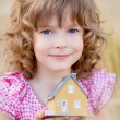 Child holding house in hands — Stock Photo