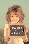 Schoolchild holding small blackboard — Stock Photo