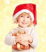 Baby holding Christmas gift in hands — Stock Photo
