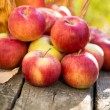 Red apples on wooden table — Stock Photo