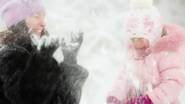 Woman and child playing with snow in winter — Stockvideo