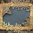 Gold Christmas tree decorations on vintage wooden blackboard — Stock Photo
