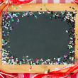 Vintage wooden blackboard with confetti  — Foto de Stock