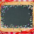 Vintage wooden blackboard with confetti — Stock Photo #33627335