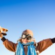 Happy kid playing with toy airplane against blue sky — Stock Photo