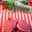 Stock Photo: Christmas tree decorations and branch on red gingham tablecloth