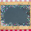 Vintage wooden blackboard with confetti  — Stock Photo