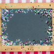 Vintage wooden blackboard with confetti — Stock Photo #34060769