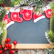 Blackboard blank framed in beautiful Christmas tree branches and — Stock Photo