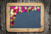 Christmas frame of confetti on blackboard — Stock Photo