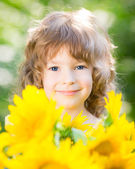 Child with bouquet of beautiful sunflowers — Stock Photo