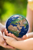 Children holding Earth in hands — Stock Photo