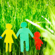 Paper family in grass — Stock Photo
