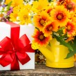 Gift box and spring flowers — Stock Photo