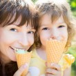 Happy child and mother eating ice cream — Stock Photo #42217559